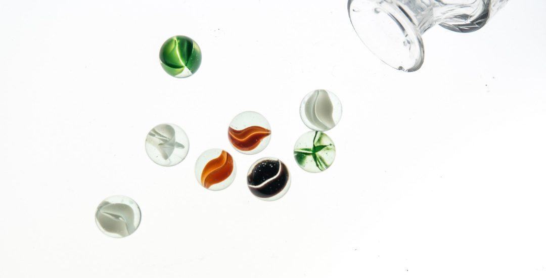 Knikkers rollend uit een glazen pot
